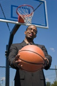 A young man in a business suit posing with a basketball.  He could be a coach player recruiter scout or trainer. Shallow depth of field with focus on the ball.