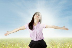 Carefree woman is stress free and holds her arms out for freedom and peace of mind.