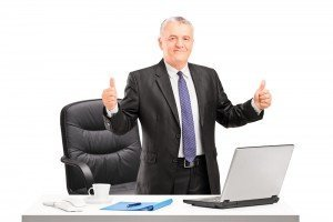Mature businessman standing in his office and giving thumbs up